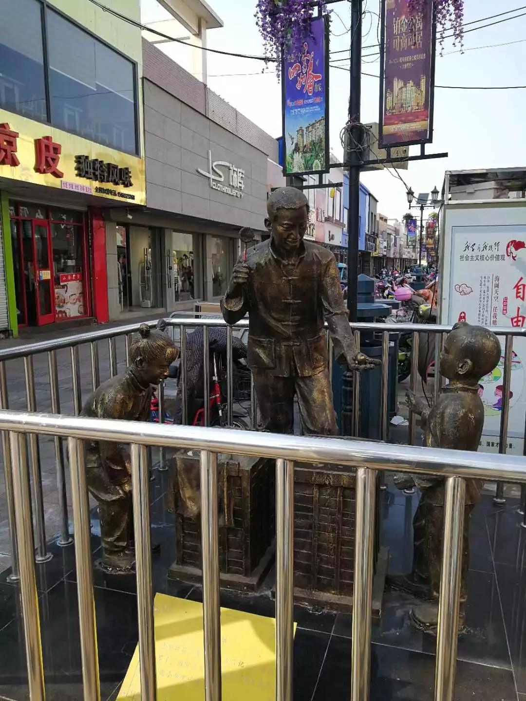 步行街内一孩童铜人像被踢倒!竟然是一十六七岁女子干的!东海人快来认认这个没素...